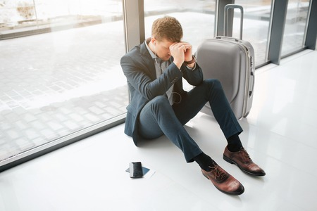 Foto de Worried and tired young man sit on floor in airport. He hide head with hands. Suitcase and phone with tickets are besides. - Imagen libre de derechos
