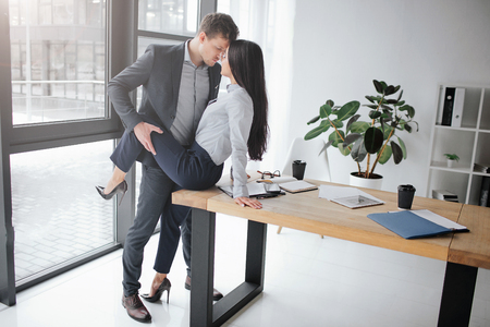 Photo for Sexual and intimate picture of couple at work. She sit on table. He hold her leg in sexual pose. They keep faces close to each other. - Royalty Free Image