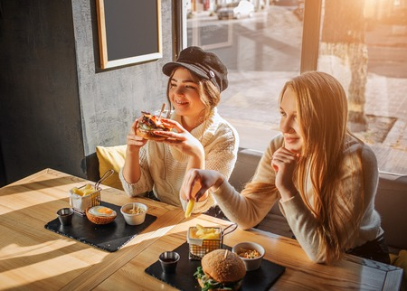 Foto für Beautiful young women sit in cafe at table. Firls has burger in hands. Another hold piece of fried potato. They enjoy eating meal - Lizenzfreies Bild