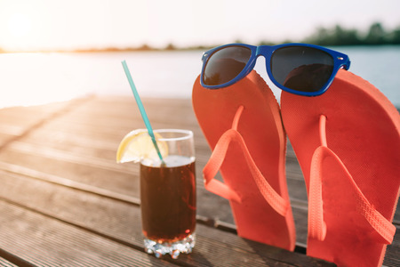 Photo for Concept of luxury vacation. Cola in glass on wooden pier. Pink flip flops with sunglasses on it. Beach party. Clear blue sky. Horizontal, wide screen format. - Royalty Free Image