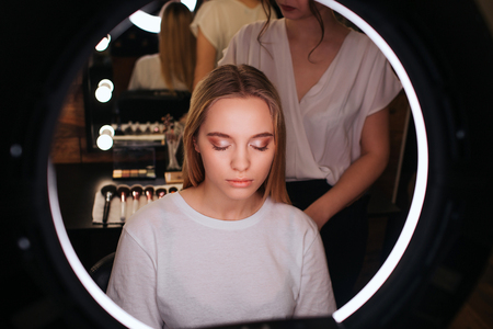 Photo pour Look in mirror. Young blonde woman keep eyes closed. She has eyeshadows on eyeline. Hairdresser stand behind her and pull hair up. - image libre de droit