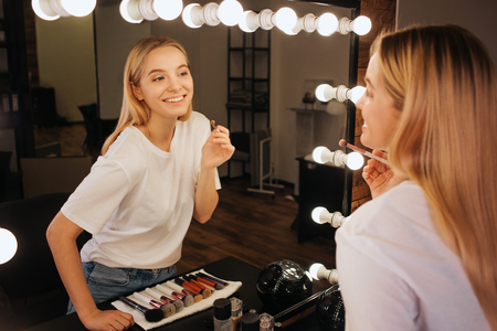 Photo pour Nice cheerful young woman look in mirror in beauty room and smile. She hold brush for eyeshadows. - image libre de droit