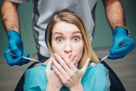 Foto de Young woman sit inchair in dentistry. She afraid and cover mouth with hands. Client look on camera with fear in eyes. Male dentist hold equipment for teeth treatment. - Imagen libre de derechos