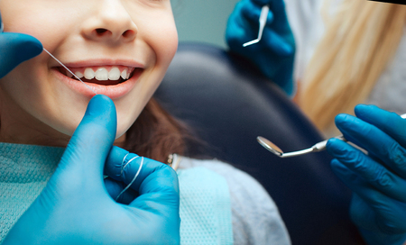 Photo for Cut view hands in latex gloves to floss child front teeth. Woman hold dental tools beside. - Royalty Free Image