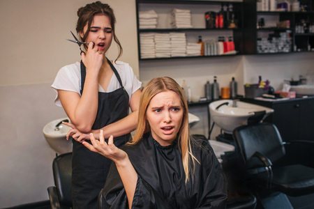 Photo pour Angry blonde young female client screaming at hairdresser as a haircut done bad in beauty salon. Badly hairstyle - image libre de droit
