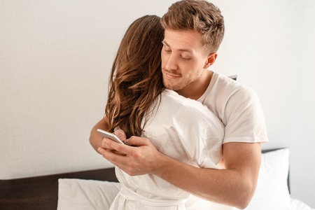 Foto de Young couple in the bedroom after waking up. Smiling unfaithful man is cheating and texting lover on the phone while hugging his girlfriend - Imagen libre de derechos