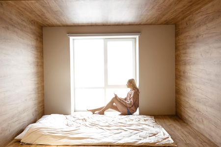 Foto de Young beautiful blonde woman sit on bed at window this morning. She hold phone and look at it with smile. Bright daylight comes out of window - Imagen libre de derechos