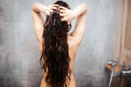 Foto de Young attractive sexy woman in shower. Dark-haired  model with well-built slim body stand and hold hair between hands. - Imagen libre de derechos