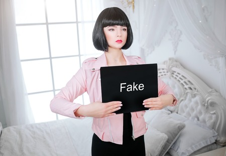 Foto de Fashion freak. Glamour synthetic girl, fake doll with empty look and short black hair is holding paper with word Fake while standing near the bed. Stylish woman in pink jacket in the white bedroom. Sexism concept - Imagen libre de derechos