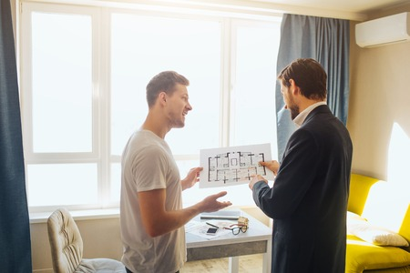 Foto de Young man and realtor buy or rent apartment. They hold one plan together. They talk and have business deal. Bright daylight comes out of window. - Imagen libre de derechos