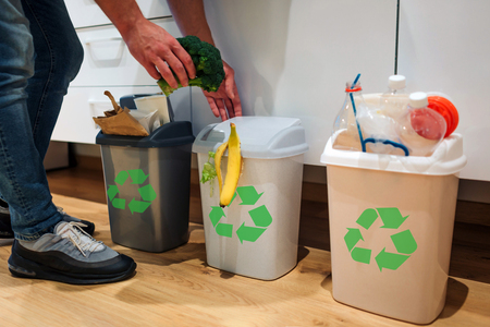 Photo pour Waste sorting at home. Cropped view of man putting broccoli in the garbage bin. Colorful trash bins for sorting waste in the kitchen - image libre de droit