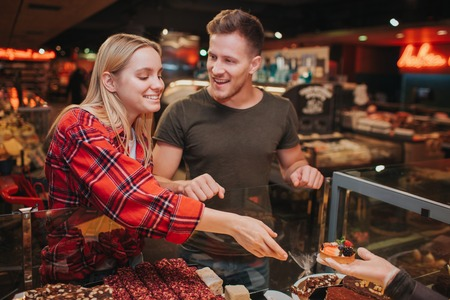 Photo pour Young couple in grocery store. Pleasant young woman get cake from hand and smile. She reach hand. Young man look at her and smile. - image libre de droit
