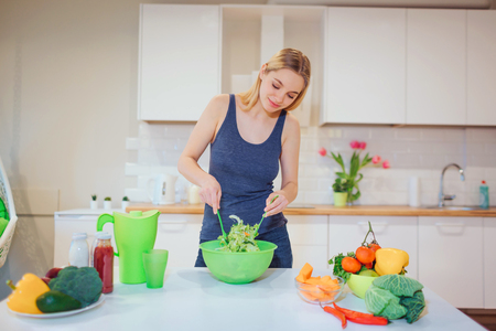 Photo pour Vegan beautiful blonde woman cooking delicious salad in the kitchen. Vegetarian food. Healthy eating. Vegan diet - image libre de droit