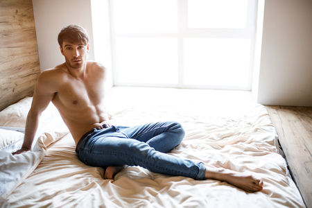 Foto per Relaxed calm and peaceful young man sitting on bed and posing on camera. Attractive handsome well-built slim guy look straight. Alone in room. Daylight. - Immagine Royalty Free