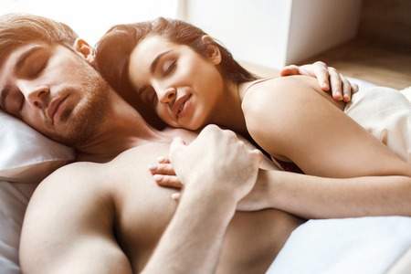 Photo for Young sexy couple after intimacy on bed. Sleeping and dreaming together. Satisfied young people happy and delightful. Woman embrace man. He hold her hand in his. Attractive models. - Royalty Free Image