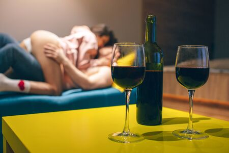 Photo pour Young couple have intimacy in kitchen in night. Seductive sensual people in sex position on sofa. Wine bottle stand on table with glasses. - image libre de droit