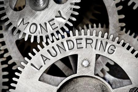 Foto de Macro photo of tooth wheel mechanism with MONEY LAUNDERING letters imprinted on metal surface - Imagen libre de derechos