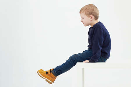 Photo pour Fashionable child in yellow boots. fashion kids.children.little boy sitting on a table - image libre de droit
