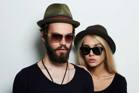 Foto de fashion beautiful couple in hat together. Hipster boy and girl. Bearded young man and blonde in sunglasses - Imagen libre de derechos