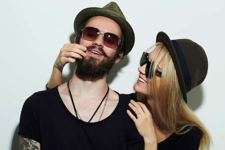 Foto de fashion beautiful happy couple in hat wearing trendy glasses together. Hipster boy and girl. Bearded young man and blonde in sunglasses - Imagen libre de derechos