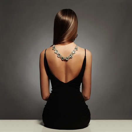 Foto de beautiful back of young woman in a black sexy dress.luxury.beauty brunette sitting girl Girl with a necklace on her back.Elegant fashion glamor photo - Imagen libre de derechos