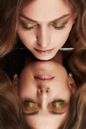 Beautiful woman with mirror reflection. Beauty model girl with make-up and curly hair
