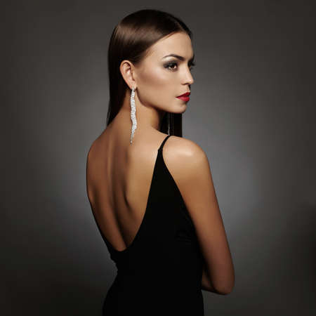 Foto de beautiful back of young woman in sexy dress.luxury beauty girl in a black sexy dress with open back wearing jewelry - Imagen libre de derechos