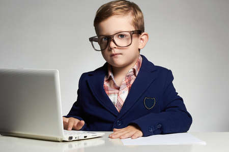 Photo for Young businessman using a laptop.little handsome boy in office.modern child - Royalty Free Image