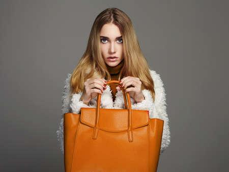 Photo pour Winter beautiful Woman with orange Handbag.Beauty Fashion Girl in fur - image libre de droit