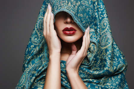 Photo pour beautiful woman covers her face with a colored cloth.red lips girl.fashion islamic style woman - image libre de droit