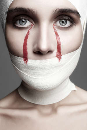 Photo for halloween style female face wrapped in bandage.girl with bloody tears.beautiful young woman fashion beauty monochrome portrait - Royalty Free Image