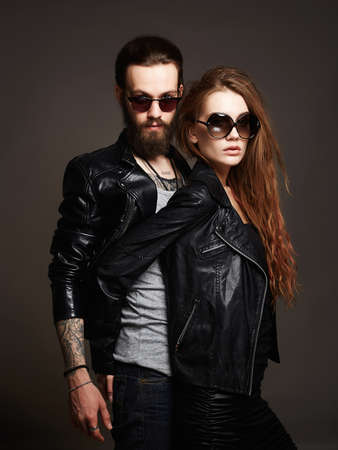 Photo pour fashion beautiful couple in sunglasses and leather.bearded man and beauty girl - image libre de droit