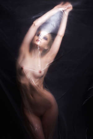 Photo for sexy girl behind a polyethylene film. beautiful nude woman. Fine-art photo. figure of a naked woman behind a transparent curtain - Royalty Free Image