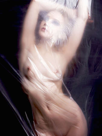 Photo for sexy nude girl behind a polyethylene film. Fine-art photo. figure of a naked woman behind a transparent curtain - Royalty Free Image