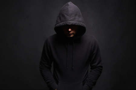 Foto de Man in Hood. Dark figure in a hooded sweatshirt. Incognito Boy - Imagen libre de derechos
