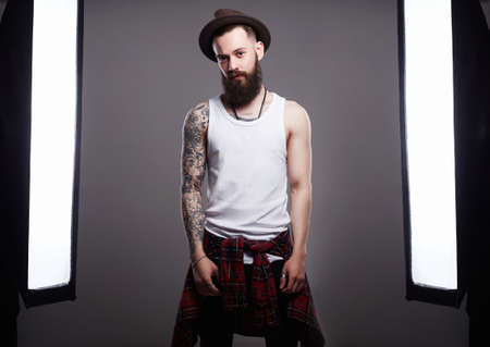 Photo for Handsome Bearded Man in Hat. Brutal hipster boy with tattoo posing in a photo studio in the middle of a photo of equipment - Royalty Free Image