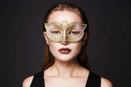 Foto de beautiful woman in golden mask. Beauty model girl in Mask - Imagen libre de derechos