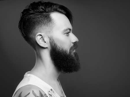 Photo for black and white portrait of handsome man with beard and tattoo. bearded hipster boy in vintage torn dirty shirt - Royalty Free Image
