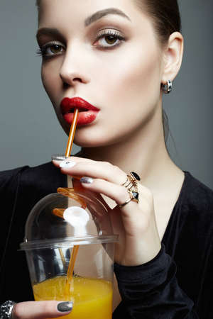 Photo pour beautiful girl drinking fresh orange juice. Healthy young woman with make-up, holding plastic glass - image libre de droit