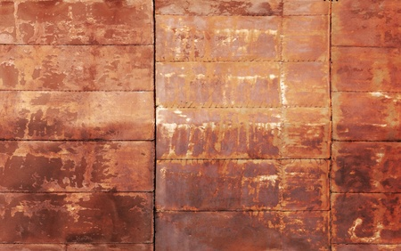 Red rusted metal wall texture with welds