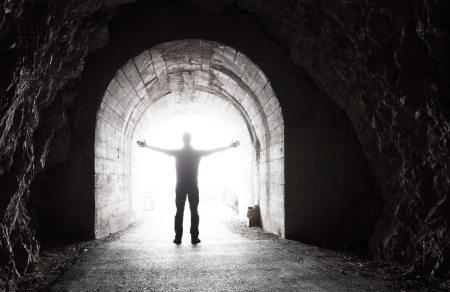 Photo pour Man stands in dark tunnel with glowing end - image libre de droit