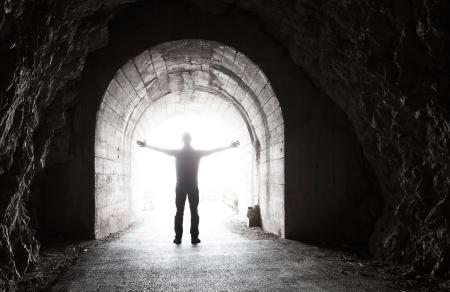 Foto de Man stands in dark tunnel with glowing end - Imagen libre de derechos