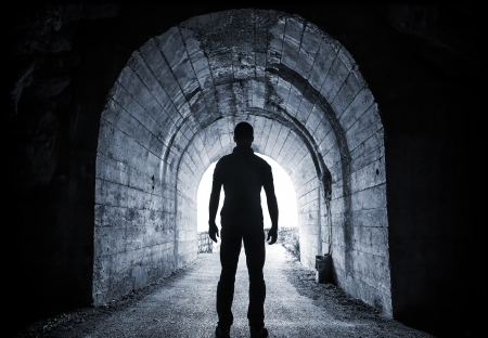 Photo pour Young man stands in dark tunnel and looks in the glowing end - image libre de droit