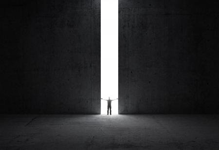 Foto de Dark abstract concrete interior  Man stands in the light of opening  - Imagen libre de derechos