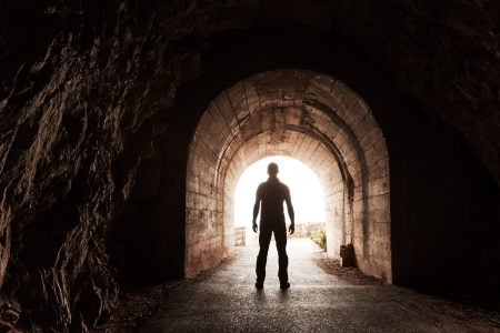 Young man stands in dark concrete tunnel and looks out in the glowing end