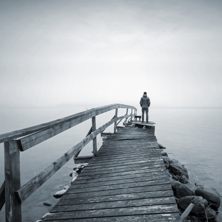 Photo for A man on the old broken wooden pier starring at the foggy Sea - Royalty Free Image