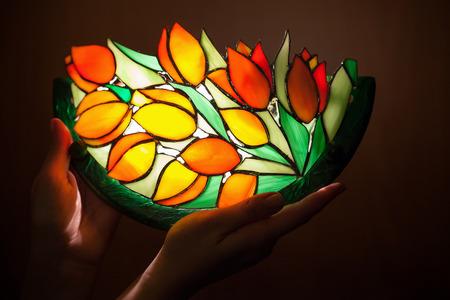 Foto de Handmade stained glass lamp with tulips flowers in woman's hands - Imagen libre de derechos