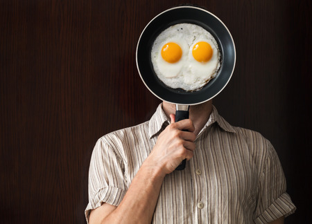 Young man portrait behind black frying pan with scrabbled eggs