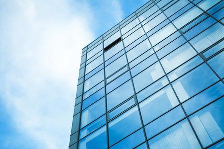 Foto de Modern office building wall made of steel and glass with blue sky - Imagen libre de derechos