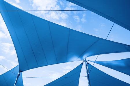Foto de Awnings in sails shape over cloudy sky background. Blue toned photo - Imagen libre de derechos